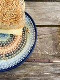 ρόλος ψωμιού με τους σπόρους και τα σιτάρια σε ένα ζωηρόχρωμο πιάτο σε έναν ξύλινο πίνακα στοκ φωτογραφία
