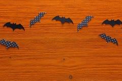 Ρόπαλα εγγράφου σε ένα πορτοκαλί ξύλινο υπόβαθρο σημειώσεις σεληνόφωτου αποκριών ροπάλων ανασκόπησης Στοκ Φωτογραφίες