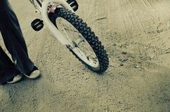 Ρόδα του ποδηλάτου και και των ποδιών με τα παπούτσια γυμναστικής Στοκ Φωτογραφία