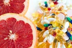 Ρόδινα γκρέιπφρουτ και χάπια, συμπληρώματα βιταμινών στο άσπρο υπόβαθρο, υγιής έννοια διατροφής Στοκ Εικόνες
