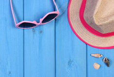 Ρόδινα γυαλιά ηλίου και καπέλο αχύρου στους μπλε ξύλινους πίνακες, εξαρτήματα για το καλοκαίρι Στοκ Εικόνες
