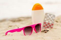 Ρόδινα γυαλιά ηλίου, κοχύλια, λοσιόν και χάπια της βιταμίνης Α, εποχιακή έννοια Στοκ Φωτογραφία