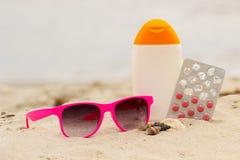 Ρόδινα γυαλιά ηλίου, κοχύλια, λοσιόν και χάπια της βιταμίνης Ε, έννοια του επιτυχούς μαυρίσματος Στοκ Εικόνες