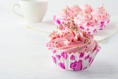Ρόδινα εύγευστα cupcakes και φλυτζάνι του τσαγιού Στοκ Εικόνα