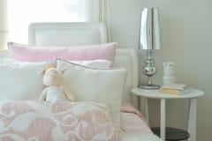 Ρόδινα και άσπρα μαξιλάρια στο κρεβάτι με τελειωμένο το χρώμιο επιτραπέζιο λαμπτήρα Στοκ εικόνες με δικαίωμα ελεύθερης χρήσης