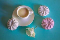 Ρόδινα και άσπρα marshmallows και φλυτζάνι με ένα cappuccino σε ένα τυρκουάζ υπόβαθρο Στοκ Φωτογραφίες