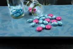 Ρόδινα και μπλε χάπια γοητείας στο μπλε υπόβαθρο Στοκ Φωτογραφίες