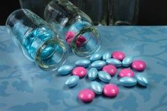 Ρόδινα και μπλε χάπια γοητείας στο μπλε υπόβαθρο Στοκ Εικόνα