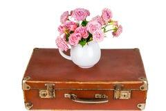 Ρόδινα λουλούδια στην κανάτα στην παλαιά καφετιά εκλεκτής ποιότητας βαλίτσα Στοκ εικόνα με δικαίωμα ελεύθερης χρήσης