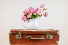 Ρόδινα λουλούδια στην κανάτα στην παλαιά καφετιά εκλεκτής ποιότητας βαλίτσα Στοκ Φωτογραφία