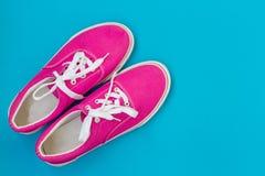Ρόδινα πάνινα παπούτσια με τις δαντέλλες σε ένα μπλε στοκ φωτογραφίες