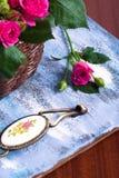 Ρόδινα τριαντάφυλλα στο καφετί καλάθι στο μπλε ξύλινο υπόβαθρο Στοκ Εικόνες