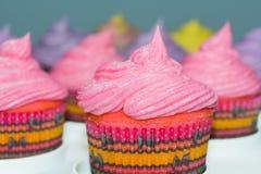 Ρόδινα cupcakes με άλλα χρώματα στο υπόβαθρο Στοκ Εικόνες
