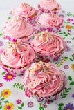 Ρόδινα cupcakes στη floral πετσέτα σχεδίων Στοκ Εικόνα