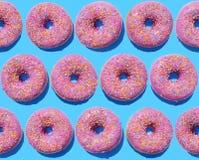 Ρόδινα doughnuts δαχτυλιδιών στο μπλε υπόβαθρο Στοκ Εικόνες