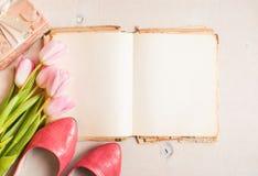 Ρόδινες τουλίπες και κενό βιβλίο με τα παπούτσια γυναικών ` s πέρα από άσπρο ξύλινο Στοκ Φωτογραφίες