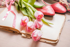 Ρόδινες τουλίπες και κενό βιβλίο με τα παπούτσια γυναικών ` s πέρα από άσπρο ξύλινο Στοκ Εικόνα