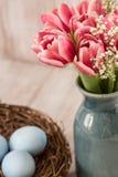 Ρόδινες τουλίπες και μπλε αυγά Πάσχας σε μια φωλιά Στοκ Εικόνες