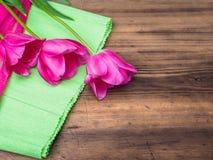 Ρόδινες τουλίπες, floral ρύθμιση στο ξύλινο υπόβαθρο με την Πράσινη Βίβλο και διάστημα για το μήνυμα Υπόβαθρο για την ημέρα μητέρ Στοκ Εικόνα