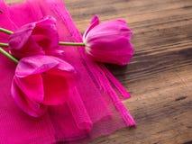Ρόδινες τουλίπες, floral ρύθμιση στο ξύλινο υπόβαθρο με το ρόδινο πλέγμα και διάστημα για το μήνυμα Υπόβαθρο για την ημέρα μητέρω Στοκ εικόνα με δικαίωμα ελεύθερης χρήσης