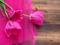 Ρόδινες τουλίπες, floral ρύθμιση στο ξύλινο υπόβαθρο με το ρόδινο πλέγμα και διάστημα για το μήνυμα Υπόβαθρο για την ημέρα μητέρω Στοκ Εικόνα