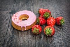 Ρόδινες doughnut και φράουλα στο ξύλινο γραφείο Στοκ Φωτογραφία