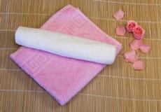 Ρόδινη, άσπρη πετσέτα με το πέταλο στο χαλί μπαμπού στοκ εικόνες