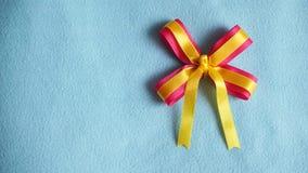 Ρόδινη και κίτρινη κορδέλλα στο μπλε υπόβαθρο υφάσματος Στοκ Εικόνες