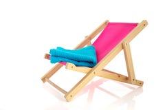 Ρόδινη καρέκλα παραλιών με την μπλε πετσέτα Στοκ εικόνα με δικαίωμα ελεύθερης χρήσης