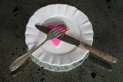 Ρόδινη καρδιά στο άσπρο πιάτο με τα μαχαιροπήρουνα Στοκ Εικόνες