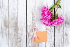 Ρόδινη κορδέλλα καρκίνου του μαστού και ρόδινα λουλούδια στο ξύλινο υπόβαθρο Στοκ εικόνες με δικαίωμα ελεύθερης χρήσης