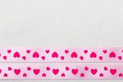 Ρόδινη κορδέλλα καρδιών στο υπόβαθρο υφασμάτων Στοκ Εικόνες