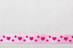 Ρόδινη κορδέλλα καρδιών στο υπόβαθρο υφασμάτων Στοκ εικόνα με δικαίωμα ελεύθερης χρήσης