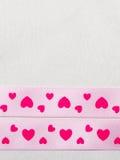 Ρόδινη κορδέλλα καρδιών στο υπόβαθρο υφασμάτων Στοκ φωτογραφία με δικαίωμα ελεύθερης χρήσης