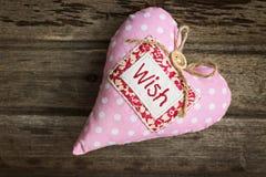 Ρόδινη μαλακή χειροποίητη υφαντική καρδιά υφάσματος με την ΕΠΙΘΥΜΙΑ λέξης στο woode στοκ φωτογραφίες με δικαίωμα ελεύθερης χρήσης