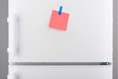 Ρόδινη σημείωση εγγράφου που συνδέεται με την μπλε αυτοκόλλητη ετικέττα στο άσπρο ψυγείο Στοκ φωτογραφία με δικαίωμα ελεύθερης χρήσης