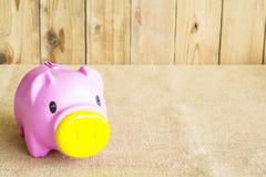 Ρόδινη piggy τράπεζα ενάντια στο ξύλο σκηνικού Στοκ Φωτογραφίες
