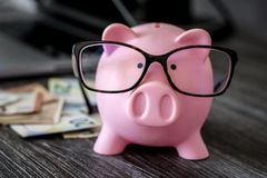 Ρόδινη piggy τράπεζα με τα γυαλιά Στοκ φωτογραφία με δικαίωμα ελεύθερης χρήσης