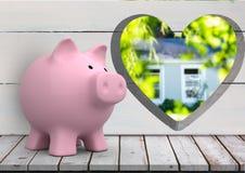 ρόδινη piggy τράπεζα μπροστά από τον ξύλινο τοίχο με την τρύπα καρδιών όπου μπορούμε να δούμε ένα σπίτι (που θολώνεται) στοκ φωτογραφία