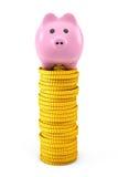 Ρόδινη piggy τράπεζα πέρα από τους χρυσούς σωρούς νομισμάτων δολαρίων Στοκ εικόνα με δικαίωμα ελεύθερης χρήσης