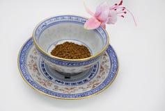 Ρόδινος φούξια και μαύρος στιγμιαίος καφές λουλουδιών σε ένα μικρά φλυτζάνι και ένα πιατάκι στοκ εικόνα με δικαίωμα ελεύθερης χρήσης