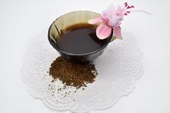Ρόδινος φούξια και μαύρος στιγμιαίος καφές λουλουδιών σε ένα μικρό φλυτζάνι σε μια άσπρη πετσέτα στοκ εικόνα