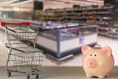 Ρόδινος piggy χοίρος τραπεζών που στέκεται κοντά στο μίνι κάρρο ώθησης αγορών με το s Στοκ Φωτογραφίες