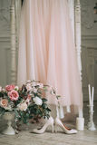 Ρόδινο γαμήλιο φόρεμα στο στούντιο, εκτός από τα μπεζ παπούτσια, μια ανθοδέσμη των τριαντάφυλλων και των κεριών Στοκ φωτογραφία με δικαίωμα ελεύθερης χρήσης