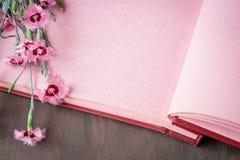 Ρόδινο εκλεκτής ποιότητας υπόβαθρο λευκωμάτων φωτογραφιών με τα λουλούδια Στοκ Εικόνες