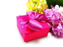 Ρόδινο παρόν Giftbox στο άσπρο υπόβαθρο με την κορδέλλα και το όμορφο λουλούδι Στοκ Φωτογραφίες