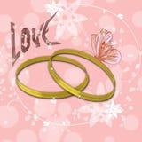 Ρόδινο υπόβαθρο με τα χρυσά δαχτυλίδια και την αγάπη επιγραφής Στοκ Εικόνες