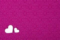 Ρόδινο υλικό με δύο καρδιές, ένα υπόβαθρο, ημέρα βαλεντίνων. Στοκ Φωτογραφία