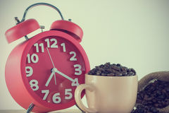 Ρόδινο φλυτζάνι με το σιτάρι καφέ και ένα κόκκινο ξυπνητήρι Στοκ Εικόνες