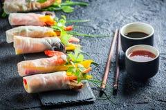 Ρόλοι άνοιξη που εξυπηρετούνται με τη σάλτσα σόγιας σε ένα πιάτο πετρών στοκ εικόνα
